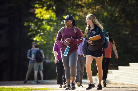 Two students with books and water bottles walking across campus. On student wears a purple jacket and grey leggings. The other student is wearing black shorts and a Lafayette jacket.
