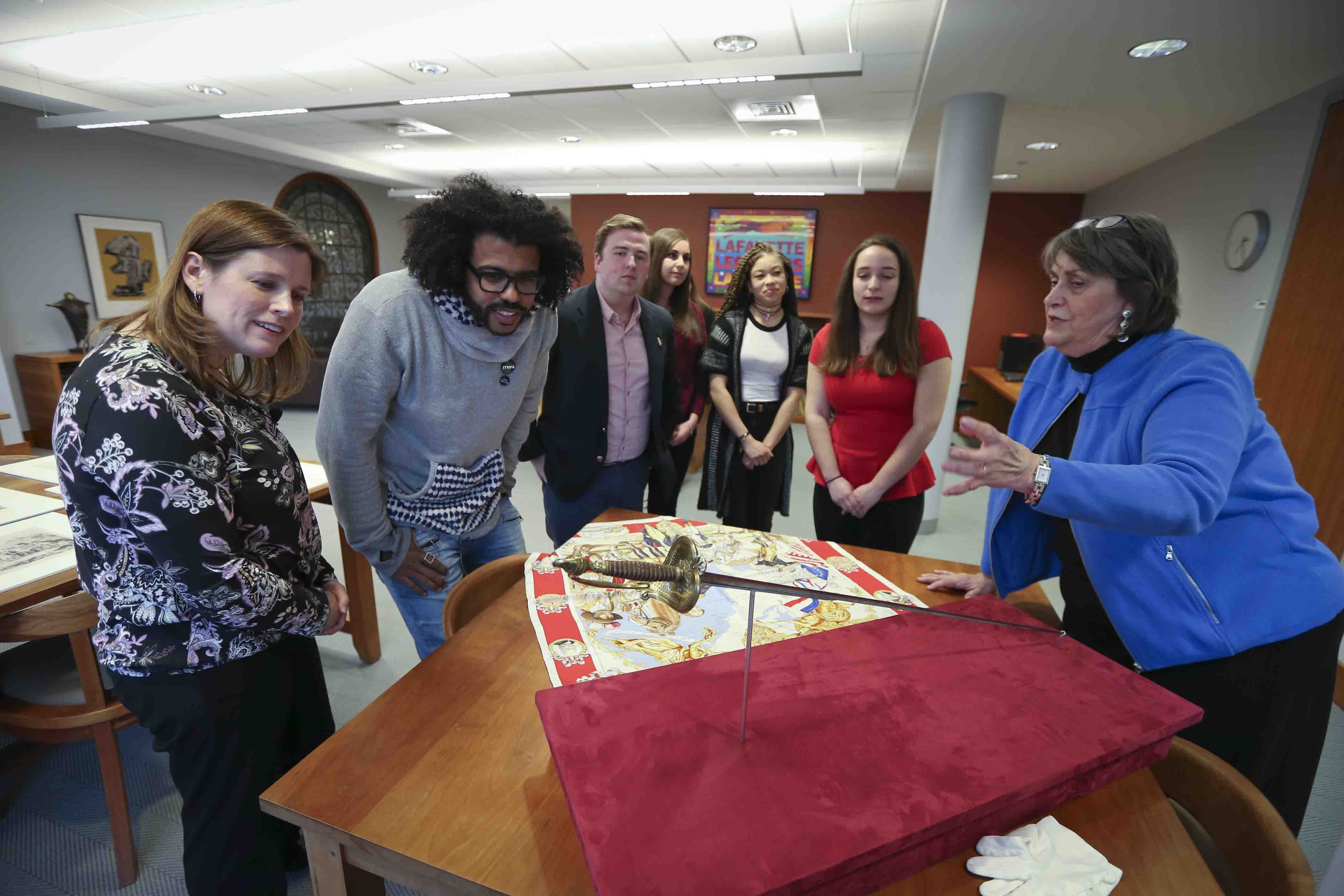 Hamilton star Daveed Diggs with Lafayette College Archivist Diane Shaw and others look at the Marquis de Lafayette's sword.